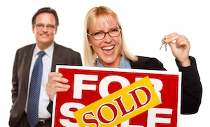 Man Behind with Attractive Blonde in Front Holding Keys and Sold For Sale Sign Isolated on a White Background.