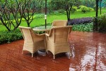 Wicker patio chairs and table near garden after raining